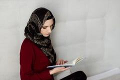 Arabische vrouw die in hijab een boek lezen stock afbeeldingen
