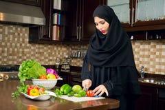Arabische vrouw die hijab het snijden veggies in de keuken dragen Stock Foto