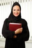 Arabische vrouw, traditionele gekleed, die zich in het bureau bevinden stock fotografie