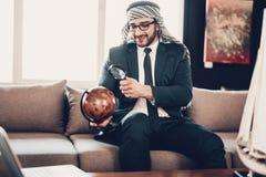 Arabische zakenman die bol met loupe bekijken royalty-vrije stock fotografie
