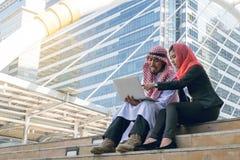 Arabische Zakenman en Onderneemster die computer met behulp van stock foto
