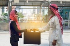 Arabische zakenman en Onderneemsterholdingszak stock afbeeldingen