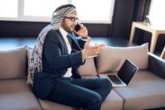 Arabischer Geschäftsmann auf dem lapton, das am Telefon auf Couch am Hotelzimmer spricht lizenzfreie stockfotografie