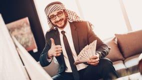 Arabischer Geschäftsmann, der Geld- und Showdaumen hochhält stockfoto