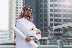 Arabischer Ingenieurbauarbeiter, der Plan hält Stockbild