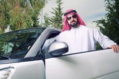 Arabischer Kerl, der zu Hause gegen sein Auto aufwirft Stockbild