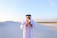 Arabischer Kerl glaubt unangenehmen Empfindungen mit der Kälte und steht in m Lizenzfreies Stockbild