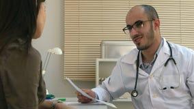 Arabischer männlicher Doktor, der Kardiogramm weiblichem Patienten erklärt stock footage