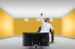 Arabischer Mann, der Fernsehapparat und das Reagieren überwacht Stockfotografie