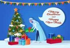 Arabischer Mann, der Geschenkbox unter der Konzeptschwätzchen-Blase der frohen Weihnachten des Tannenbaumguten rutsch ins neue ja lizenzfreie abbildung