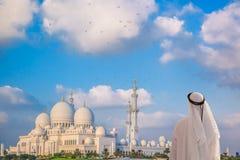 Arabischer Mann, der Sheikh Zayed Grand Mosque in Abu Dhabi, Vereinigte Arabische Emirate aufpasst Lizenzfreie Stockfotos