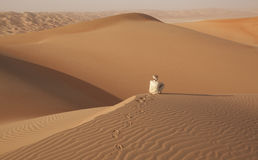 Arabischer Mann in der traditionellen Ausstattung, die in der arabischen Wüste sitzt und die Landschaft genießt Lizenzfreie Stockfotografie