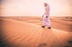 Arabischer Mann mit traditionellen Emiraten kleidet das Gehen im dese Lizenzfreie Stockbilder