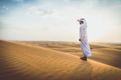 Arabischer Mann mit traditionellen Emiraten kleidet das Gehen im dese Stockfotos
