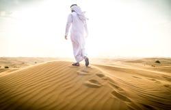 Arabischer Mann mit traditionellen Emiraten kleidet das Gehen im dese Stockfotografie