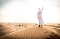 Arabischer Mann mit traditionellen Emiraten kleidet das Gehen im dese Stockfoto