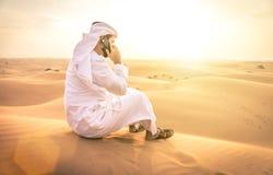 Arabischer Mann mit traditionellen Emiraten kleidet das Gehen im dese Lizenzfreies Stockbild