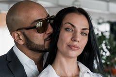 Arabischer Mann umarmt und küsst ein hübsches Mädchen Stockbild