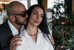 Arabischer Mann umarmt und küsst ein schönes Mädchen Stockfotografie