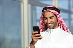 Arabischer saudischer Geschäftsmann, der mit seinem Telefon arbeitet Lizenzfreies Stockbild