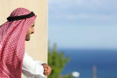 Arabischer saudischer Mann, der das Meer von einem Balkon eines Hotels schaut Lizenzfreies Stockfoto