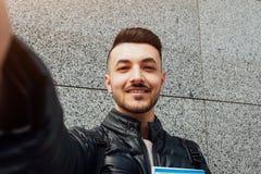 Arabischer Student nimmt selfie auf Smartphone draußen Glücklicher Kerl betrachtet Telefon durch die Wand nach Klassen stockfoto
