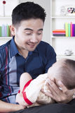 Arabischer Vater, der am Baby lächelt Lizenzfreie Stockfotos