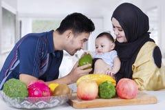 Arabischer Vater, der seinem Baby Frucht gibt Lizenzfreie Stockfotografie