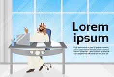 Arabisches Geschäftsmann-Gespräch am Telefon, das am Schreibtisch mit Laptop-Berechnung sitzt Stockfotografie