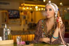 Arabisches Mädchen, welches das Hukarohr in einer Kaffeestube hält Lizenzfreie Stockfotos