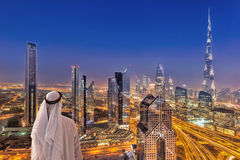 Arabisches Stadtbild des Mannes aufpassende Nachtvon Dubai mit moderner futuristischer Architektur in Vereinigte Arabische Emirat Lizenzfreies Stockbild