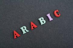 ARABISCHES Wort auf dem schwarzen Bretthintergrund verfasst von den hölzernen Buchstaben des bunten ABC-Alphabetblockes, Kopienra Stockfotos