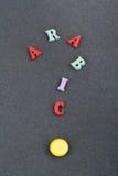 ARABISCHES Wort auf dem schwarzen Bretthintergrund verfasst von den hölzernen Buchstaben des bunten ABC-Alphabetblockes, Kopienra Stockfoto