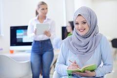 Arabisk affärskvinna i startup kontor med laget som arbetar i bakgrunden, royaltyfria bilder