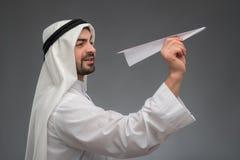 Arabisk affärsman med det pappers- flygplanet Arkivfoton