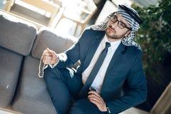 Arabisk affärsman med pärlor på soffan på hotellrum royaltyfria foton