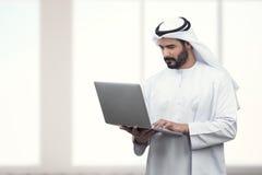 Arabisk affärsman som använder anteckningsboken i ett modernt kontor Arkivfoton