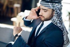 Arabisk affärsman som talar på telefonen på soffan på hotellet Royaltyfri Fotografi