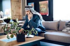 Arabisk affärsman som talar på telefonen på soffan på kontorsrum Royaltyfria Foton