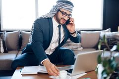 Arabisk affärsman som talar på telefonen på soffan på kontorsrum Arkivbild