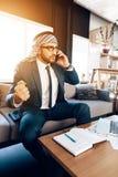Arabisk affärsman som talar på telefonen på soffan på kontorsrum Royaltyfri Bild