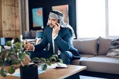 Arabisk affärsman som talar på telefonen på soffan på kontorsrum Arkivfoton