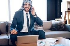 Arabisk affärsman som talar på telefonen på soffan på kontorsrum Arkivbilder