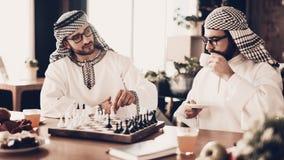 Arabisk affärsman som två spelar schack på tabellen royaltyfri fotografi