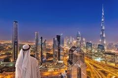 Arabisk cityscape för hållande ögonen på natt för man av Dubai med modern futuristisk arkitektur i Förenade Arabemiraten Royaltyfri Bild