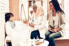 Arabisk doktor Give Medicine till liggande säng för sjuk pojke Säker muslimsk kvinnlig doktor Giving Glass av medicin Barn på royaltyfri bild