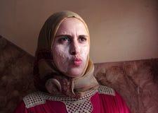 Arabisk egyptisk muslimkvinna som applicerar den ansikts- maskeringen Arkivfoto