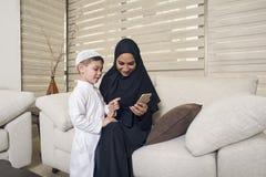 Arabisk familj, arabisk moder och son som använder mobiltelefonen royaltyfri fotografi