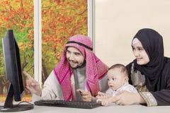 Arabisk familj som ser datoren Arkivfoton