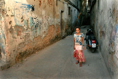 Arabisk flicka med den färgrika klänningen som står i den förfallna borggården Fotografering för Bildbyråer